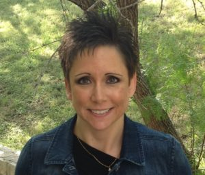A photo of Tracy Grinstead-Everly. She has short, dark hair with brown eyes and is wearing a dark denim jacket.